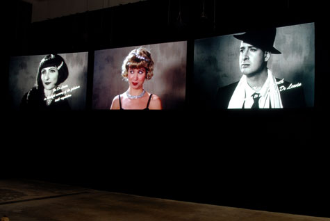 three screens with peoples' faces in a dark exhibition space