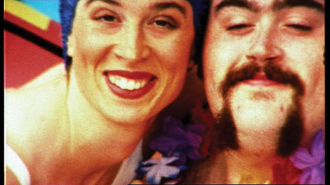 Bright colour image of man with a beard smiling waring a Hawaiin garland next to a girl with a swimming hat smiling too