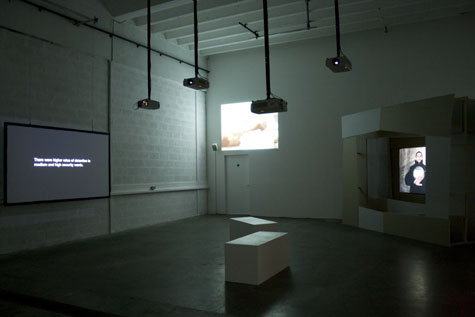 large concrete gallery space with video projection and suspended video projectors