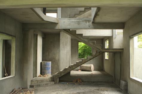 interior of disused concrete building with staircase