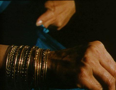 woman's hands with bangles folding a sari