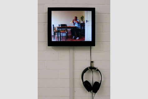 flatscreen monitor on white brick wall with headphones hanging from hook