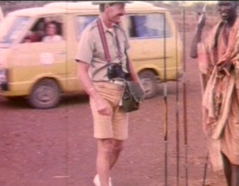 old film still showing man in western costume and man in African tribal costume