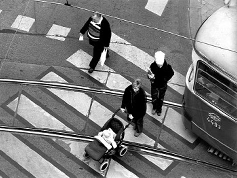image of people crossing at a crossing behind a tram