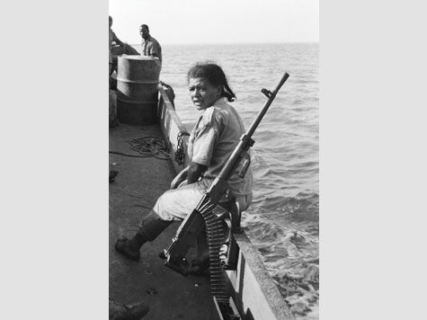 black and white image of a woman on a boat with a gun