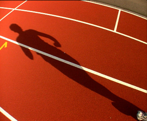 Image of a shadow on a red running track