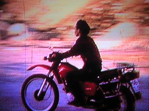 degraded video image of a woman on a motorbike