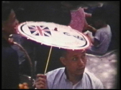 old film still of man holding paper parasol with Union Jack