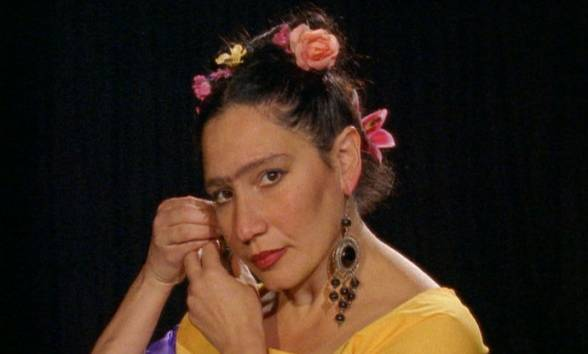 Image dressed as Frida Kahlo with flowers in her hair putting earings on