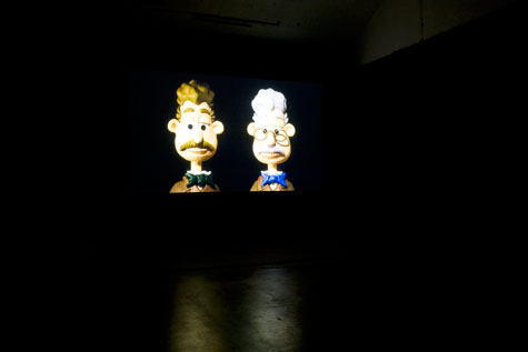 large video projection of two grey haired plasticine characters in blacked out gallery