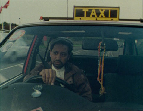 image of a man driving a taxi, around his rear view mirror there are beads hanging