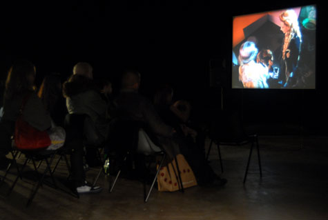 people in a dark space watching a large film on a screen