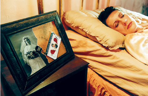 woman in 1940s costume asleep in bed, torn photograph in a frame alongside the bed