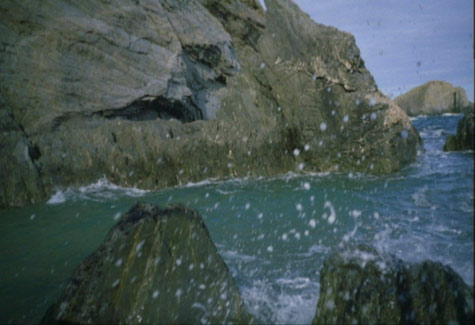image of a rough sea hitting against rocks, bits of water and see are spashing up infont of the camera
