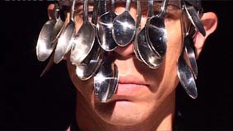 man's face with sliver spoons in front of his eyes