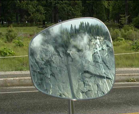 image of rocky cliffs and trees reflected in an old fashioned car wing mirror