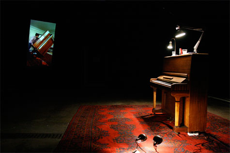 video projection in dark gallery with a piano and red rug